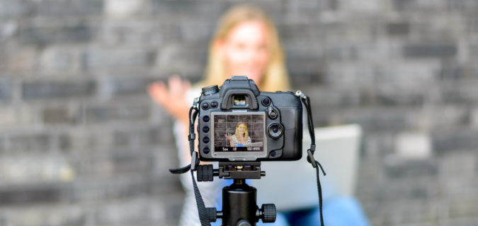 Young woman in focus on digital camera LCD screen waving hand while seated on ground against wall for concept about video blogging
