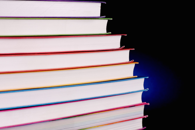 A stack of thin books of same sizes, with white pages and colorful flexicovers arranged on a semi rainbow order. They are standing in the dark, in front of a black background lit by a small deep blue spot.